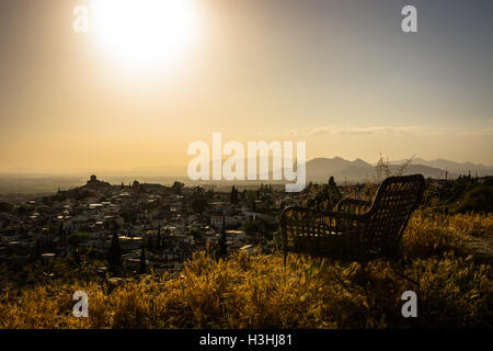 A chair at a lookout. Sit down and relax. Do nothing for awhile, just breathe and see the how the Sun goes down. - Stock Photo