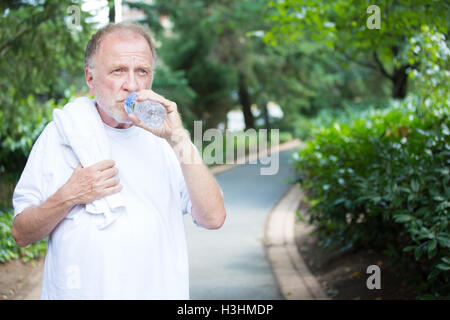 Closeup portrait, thirsty senior mature man in white shirt with towel, drinking water outside, isolated green tree - Stock Photo