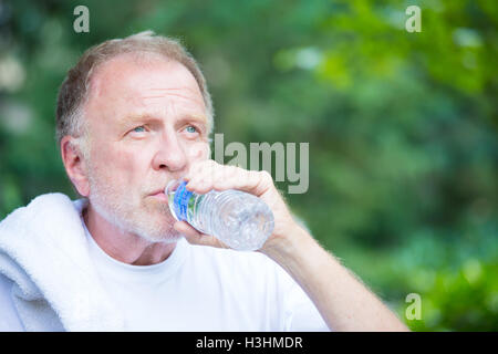 Closeup portrait, thirsty senior mature man drinking water outside, isolated green tree foliage background - Stock Photo