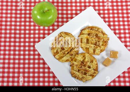 apple pie cookies with caramel candy on white square plate with green apple - Stock Photo