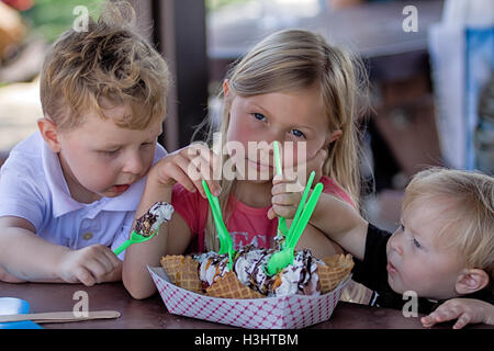 Young girl forced to share her ice cream sundae with her younger brothers. - Stock Photo