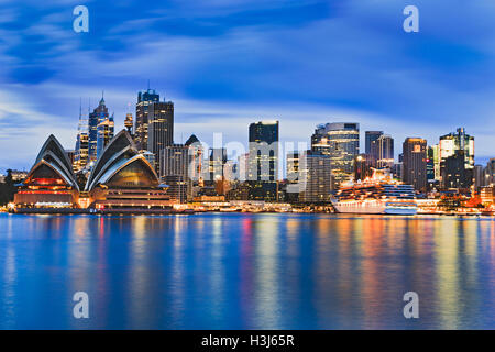 Cityscape of Sydney city CBD across Harbour at sunrise reflecting bright lights of skyscrapers and major landmark - Stock Photo