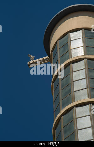 A surveillance camera mounted on the top of a tall building - Stock Photo