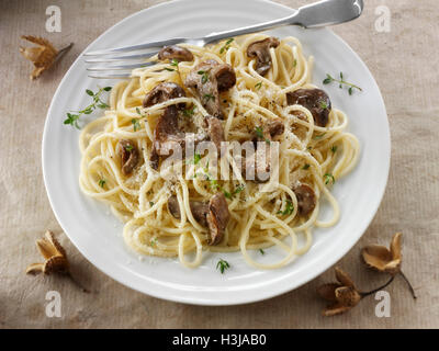 Sauteed wild organic Pied Bleu Mushrooms (Clitocybe nuda), Blewit or Blue Foot mushrooms cooked in butter with spaghetti - Stock Photo