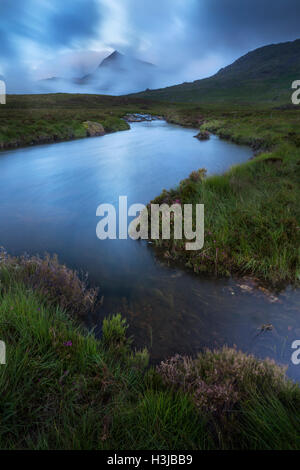 Nant Gwryd flows from Llyn Cwmffynnon in the cool blue dawn light. Crib Goch and the Snowdon Horseshoe is shrouded - Stock Photo