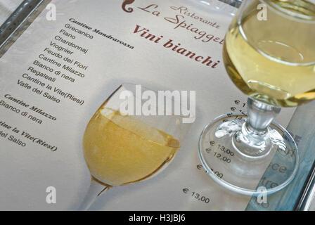 WINE LIST SICILY Glass of Sicilian white wine on wine menu list in Ristorante La Spiaggetta Sicily with typical - Stock Photo