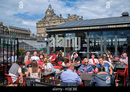 Customers enjoying a drink at Wetherspoon's on Waverley Bridge, Edinburgh with the Balmoral Hotel in the background. - Stock Photo