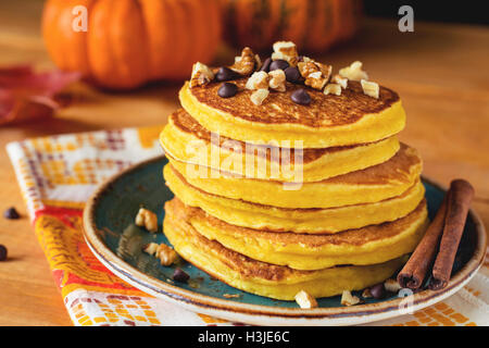 Pumpkin pancakes with nuts and chocolate on plate. Close up. Autumn breakfast meal, traditional American cuisine - Stock Photo