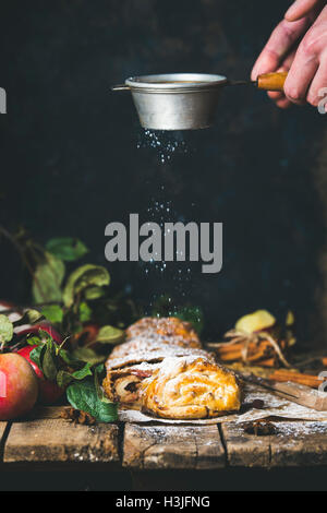 Apple strudel cake cut in pieces with fresh red apples on rustic wooden table and man's hands with sieve sprinkling - Stock Photo