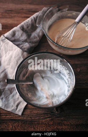 Eggs, sugar, milk, flour batter in a glass bowl and whipped eggs whites in a mixing bowl on a wooden table - Stock Photo