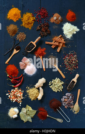 Colorful spices and herbs on a dark wooden table - Stock Photo