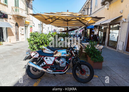 Street of the old town of Olbia with people walking, bar terraces and Guzzi motorcycle in foreground in Sardinia, - Stock Photo