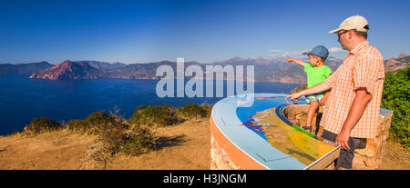 Father and his son on the viewport near Piana with stunning Corsica coastline and Golfe de Porto and Girolata, Corsica, - Stock Photo
