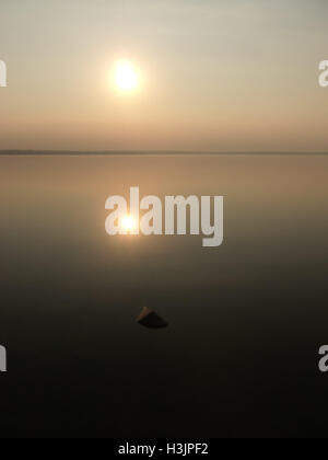 Setting sun and glassy smooth water, Lake Unden, Sweden - Stock Photo