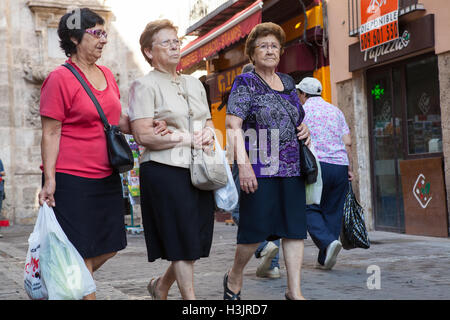 Three old women walking through the streets of the old quarter in Valencia - Stock Photo