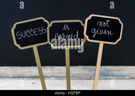 Business message SUCCESS IS EARNED, NOT GIVEN written with chalk on wooden mini blackboard labels - Stock Photo