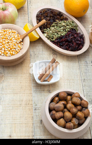 Wooden table with dry fruits and various seeds, cinnamon and other ingredients for healthy meal - Stock Photo