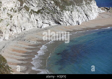 Looking across man of war bay at the patterns created by the tidal flow on the sand and shingle beach with white - Stock Photo