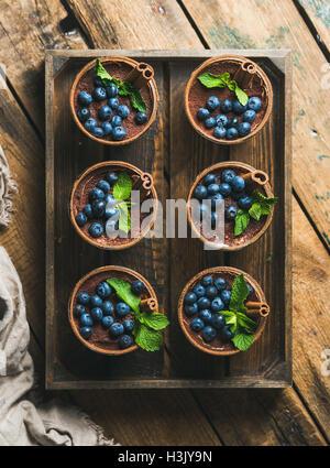 Homemade Tiramisu dessert with cinnamon and berries in wooden tray - Stock Photo
