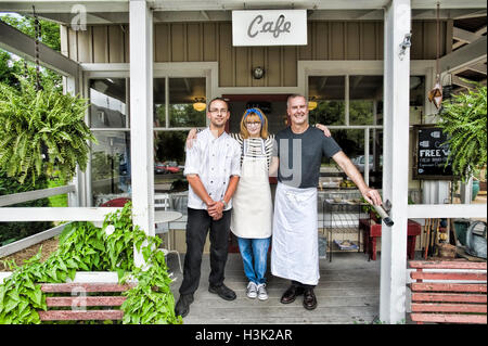 Cafe owner and partners posing in front of restaurant - Stock Photo