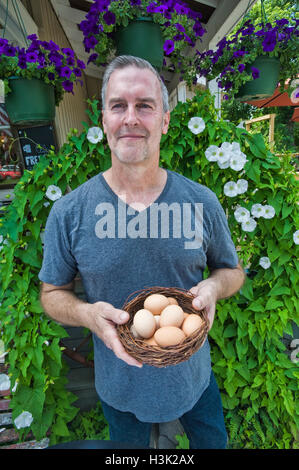 Cafe owner carrying basket of fresh eggs in front of restaurant - Stock Photo