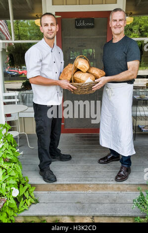Cafe owner and chef with basket of bread in front of restaurant - Stock Photo