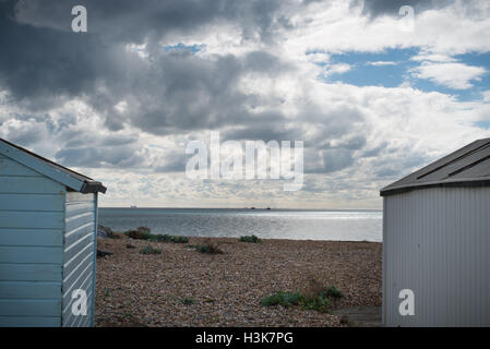 A dramatic sky full of clouds above beach huts on the beach at Lancing, West Sussex, England. - Stock Photo