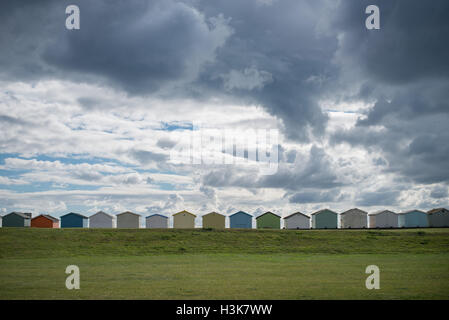A dramatic sky full of clouds above beach huts on the seafront at Lancing Green, Lancing, West Sussex, England. - Stock Photo