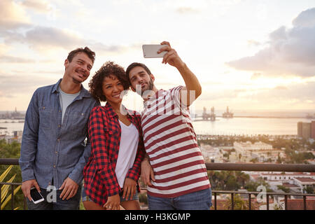 Three happy young people on a bridge taking selfies with a city and lake behind them while wearing casual clothing - Stock Photo