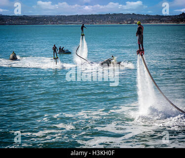 GB - DEVON: Flyboarders off Torquay Promenade with Paignton in background - Stock Photo