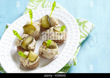 Canapes with fish pate and pickle - Stock Photo
