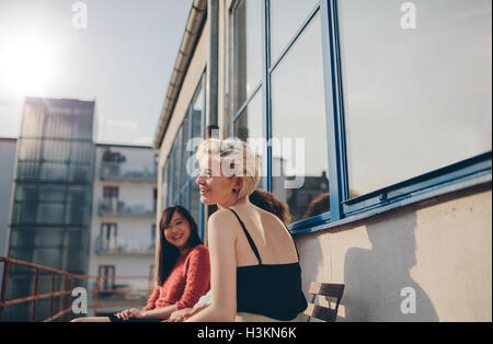 Three young women sitting in balcony on a sunny day. Female friends enjoying free time together outdoors. - Stock Photo