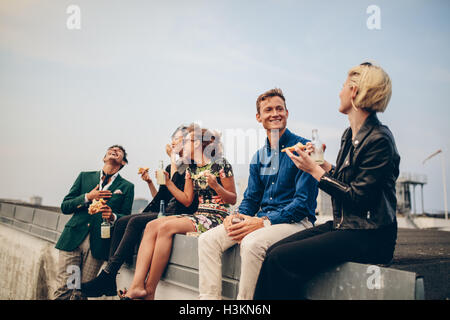 Group of friends partying on terrace, drinking and eating. Young men and women enjoying drinks on rooftop. - Stock Photo