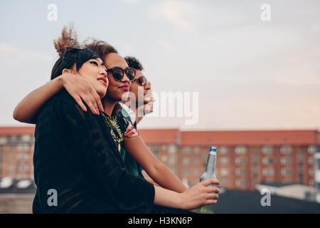 Shot of young people partying on terrace. Multiracial friends sitting together on rooftop having drinks. - Stock Photo