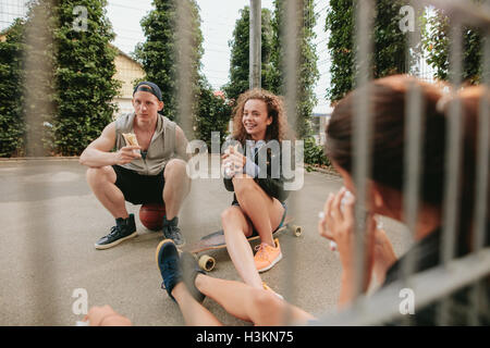Group of friends sitting at outdoor basketball court eating and having fun. Teenagers relaxing basketball court. - Stock Photo