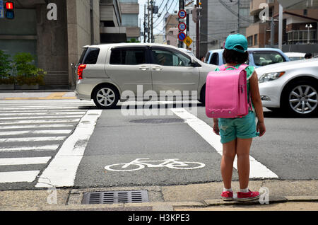 Children japanese girl waiting cross over road at crosswalk traffic road after finished study class at school near - Stock Photo