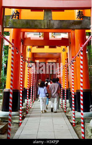 Japanese people and traveler foreigner walking travel and visit on pathway inside through a tunnel of torii gates - Stock Photo
