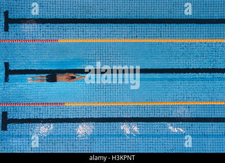 Top view shot of young man swimming laps in a swimming pool. Male swimmer gliding through the water. - Stock Photo