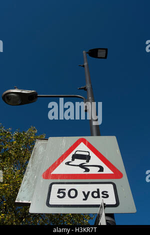 british road sign warning of a slippery road surface 50 yards ahead, in hounslow, middlesex, england - Stock Photo