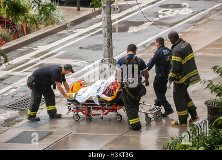 Emergency Medical Technicians  and FDNY firefighters transfer an obese in New York on Friday, September 30, 2016. - Stock Photo