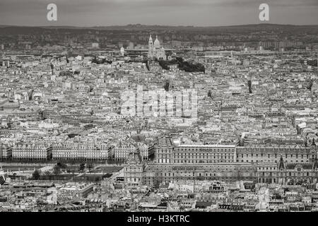 Aerial view of Paris rooftops with The Louvre, Tuileries Garden and Sacre Coeur Basilica in Montmartre. France (Black - Stock Photo