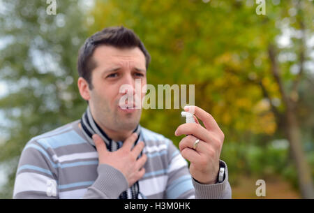 Young man using throat spray in cold season - Stock Photo