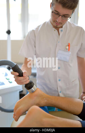 Physiotherapist performs ultrasound physical therapy treatment - Stock Photo