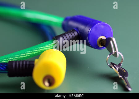 bicycle lock with key on green table isolated - Stock Photo