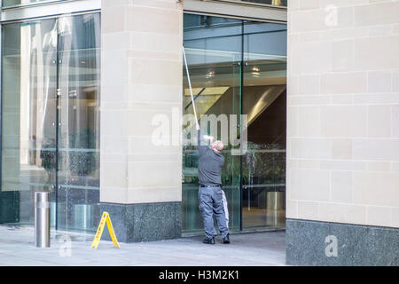 Window cleaner cleaning windows on an office building in London - Stock Photo