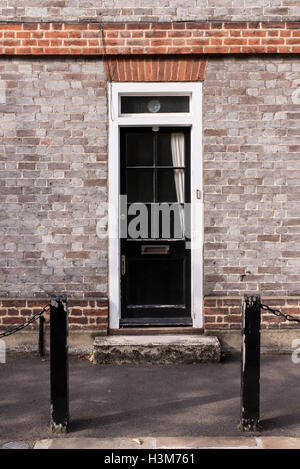 Victorian black external wooden door with glass panels on a classic grey brick wall - Stock Photo