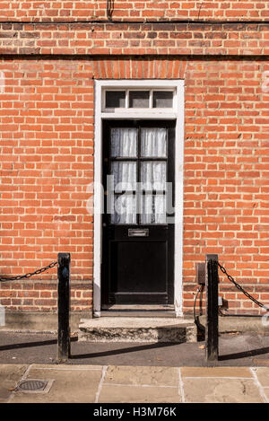 Victorian black external wooden door with glass panels on a classic red brick wall - Stock Photo