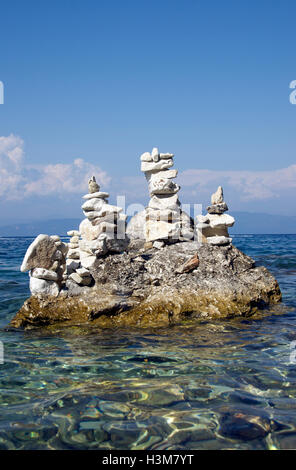 Stone balancing Gaios Harbour Paxos Ionian Islands Greece - Stock Photo
