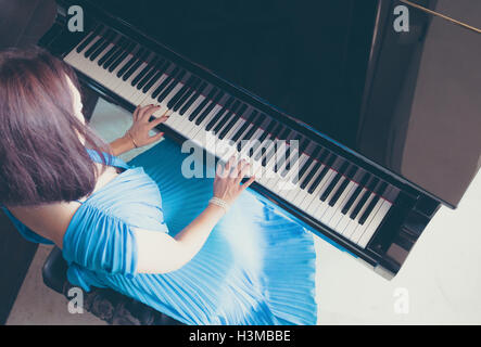 lady in blue dress playing a piano - Stock Photo