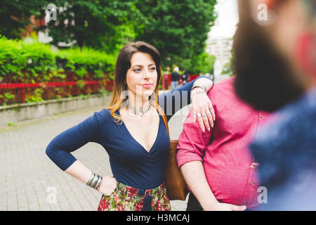 Group of friends chatting by roadside - Stock Photo